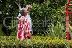 Smiling senior couple walking together amidst plants