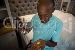 Senior man taking medicine while sitting in bedroom