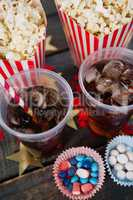 Popcorn, confectionery and drink arranged on wooden table with 4th july theme