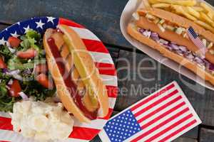 Hot dog and American flag on wooden table