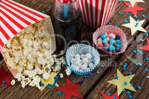Scattered popcorn and sweet food decorated with 4th july theme