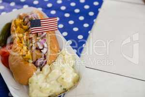 American flag and hot dog on wooden table