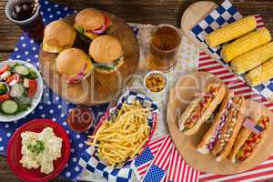 Hot dogs and burgers on wooden table with 4th july theme