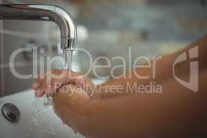 Girl washing hands in bathroom sink