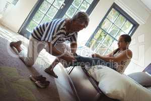 Grandmother helping granddaughter to wear socks in bed room