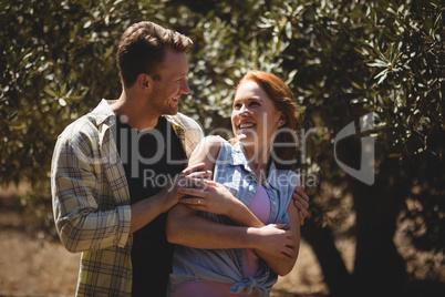 Playful young couple enjoying at olive farm