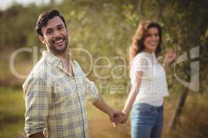 Handsome young man holding woman at olive farm