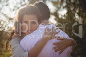 Portrait of young woman hugging boyfriend
