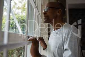 Senior man wearing eyeglasses while looking out through window