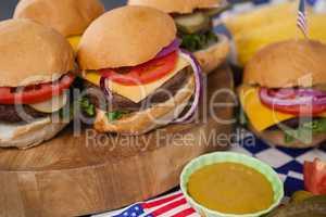 Hamburger with mustard sauce on wooden board