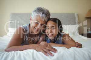 Grandmother and granddaughter relaxing on bed in bed room