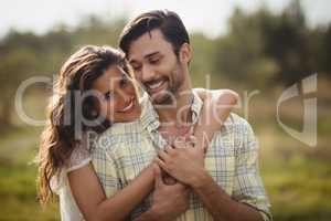 Young woman embracing man on sunny day at farm