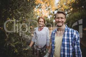 Smiling young couple standing by olive trees at farm