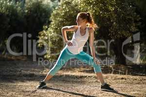 Young woman stretching on field at farm