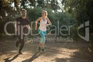 Young couple running during sunny day at farm