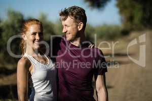 Young woman with man standing at farm on sunny day