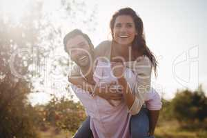 Handsome young man piggybacking woman at farm