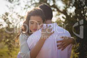 Young woman hugging boyfriend at farm
