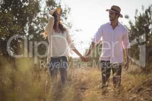 Happy young couple holding hands at farm