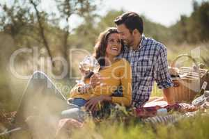 Happy young couple holding wineglasses while relaxing on picnic blanket