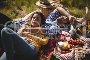 Young couple relaxing on picnic blanket at olive farm