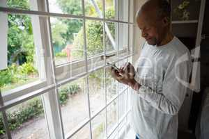 Senior man using mobile phone by window at home