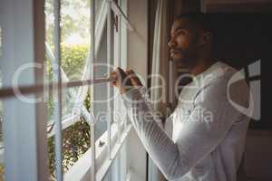Thoughtful man looking out through window at home