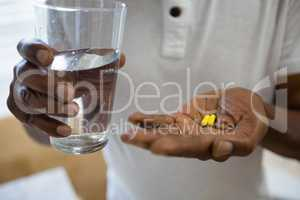 Mid section of senior man holding medicines and drinking water