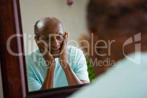Reflection of concerned senior man on mirror