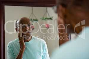Concerned senior man rubbing cheek while looking into mirror