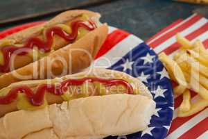 Hot dog served on plate with french fries