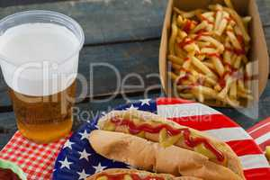 Hot dog served on plate with french fries and beer