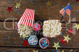 Popcorn, sweet food and cold drink decorated with 4th july theme