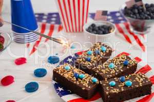 Close-up of sweet food and burning crackers decorated with 4th july theme