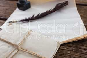 Quill feather, ink pot, and legal documents arranged on table