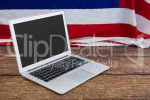 Laptop and American flag on wooden table