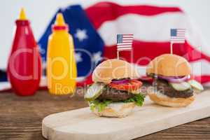Burgers arranged on wooden board