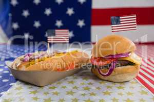 Burger and hot dog on wooden table with 4th july theme