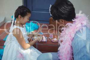 Father and daughter in fairy costume having a tea party