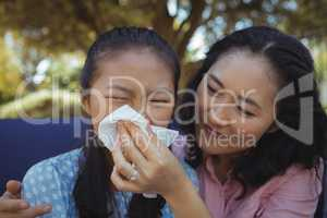Mother helping daughter blow her nose