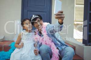 Father and daughter in fairy costume taking a selfie