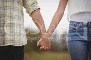 Mid section of couple holding hands at farm