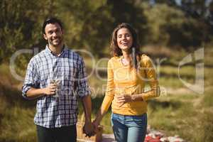 Happy young couple holding wineglasses at farm