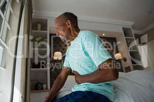 Side view of senior man suffering from stomachache at home