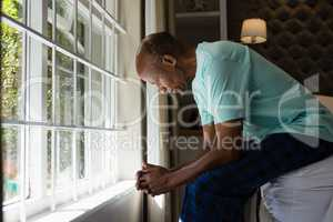 Senior man sitting by window in bedroom at home
