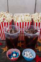 Popcorn, confectionery and drink on wooden table