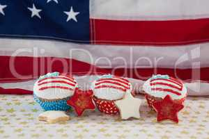 Close-up of decorated cupcakes and cookies arranged on table