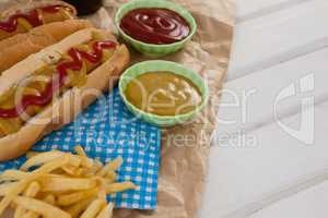 Hot dog, french fries and sauces on brown paper
