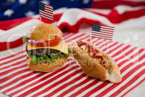 American flag with hot dog and burger on wooden table
