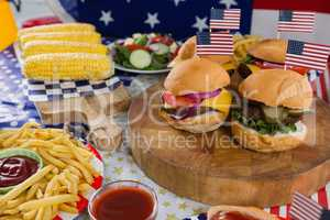 Burgers and corn cob on wooden table with 4th july theme